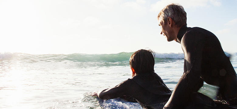 Father and son surfing on a sunny day