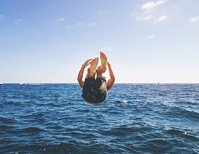 Young man diving backwards into the ocean
