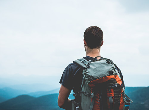 Young man with backpack looking into the distant mountains