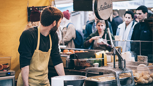 Young man wearing apron serving customers at busy food stall