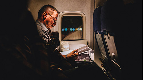 Man reading paperwork on an airplane