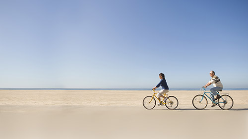 A retired couple riding bicycles along the beach on a sunny day